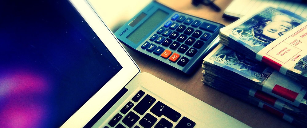Stack of money next to a calculator and laptop