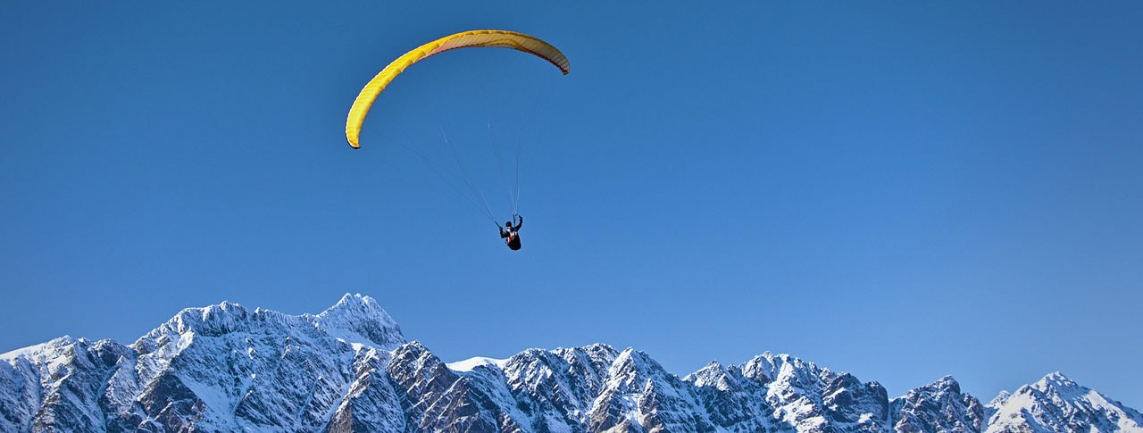 Paraglider over snow capped mountains